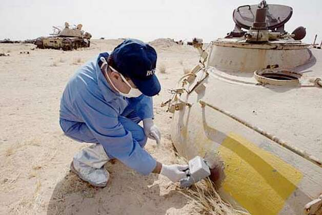 In southern Iraq, Dr. Klajak Varjaanian holds a Geiger counter next to an Iraqi tank destroyed by a depleted uranium weapon; the radiation level was 1,000 times normal. Seattle Post-Intelligencer photo by Paul Kitagaki Jr.
