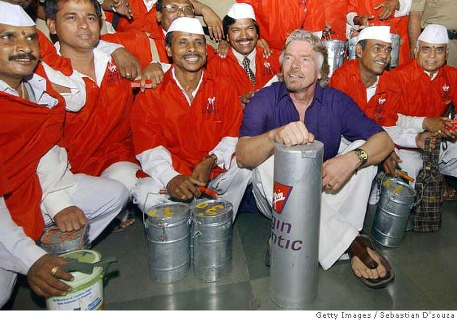 Chairman of Britain's Virgin Atlantic Airline Sir Richard Branson (2R) poses with Dabbahwallahs (tiffin carriers) while sitting with a Virgin Atlantic 'tiffin box' after alighting from a train at Churchgate Railway Station in Bombay, 01 April 2005. Branson who is on a two-day visit to the city has launched Virgin Atlantic's thrice-a-week London-Bombay flight. Virgin Atlantic Airways first flight to India's financial and entertainment capital Bombay, marks the launch of a second Indian route, the airline already operates daily services to India's capital city Delhi. Bombay's Dabbahwallahs are renowned for their delivery system of lunchboxes or tiffin's to office workers from the city's suburbs. AFP PHOTO/Sebastian D'SOUZA (Photo credit should read SEBASTIAN D'SOUZA/AFP/Getty Images) Photo: SEBASTIAN D'SOUZA
