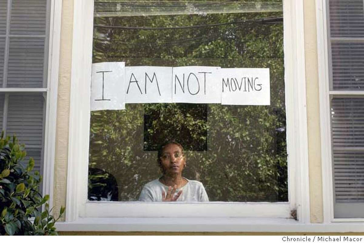 """mccullough_022_mac.jpg Daphne McCullough peers from her front window with the sign she recently put up. Patrick McCullough is not moving, and his wife Daphne hung a banner in the window of thier 59th St. home telling the world, """"I Am Not Moving"""" it says. Their reason for staying put-against the advice of police that McCullough could be a target for shooting a 16 year-old neighbor with a group of youths outside his home two months ago-are practical and philosophical. They can't afford to move and they're not sure they can sell given the bad publicity. And they don't want to be seen as giving in to drug dealers. 4/7/05 Oakland, Ca Michael Macor / San Francisco Chronicle Mandatory Credit for Photographer and San Francisco Chronicle/ - Magazine Out"""