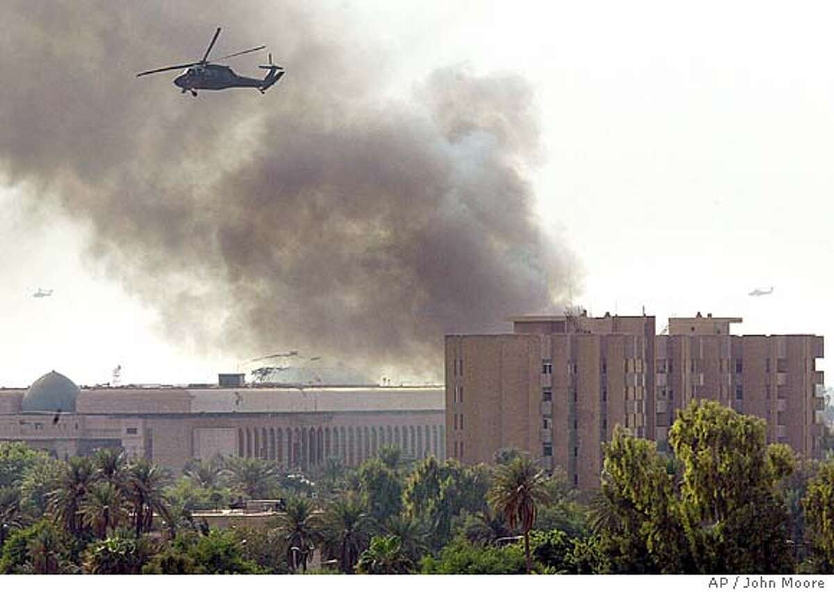 An American helicopter passes over after two explosions in the heavily fortified Green Zone in Baghdad, Iraq Thursday, Oct. 14, 2004. The Green Zone is home to the U.S. Embassy and Iraqi government offices.(AP Photo/John Moore)