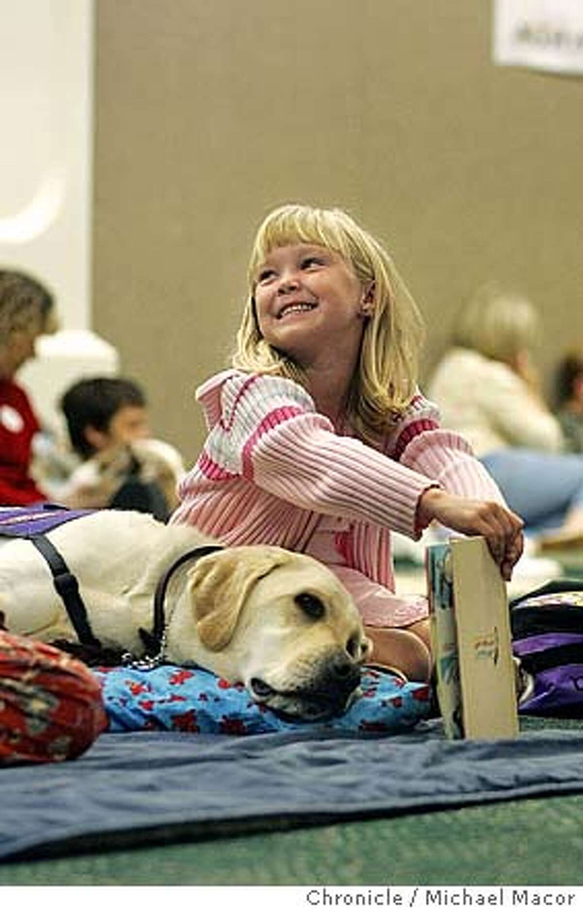 """6 year old Maura Carrick enjoying her time with, """"Ben"""". PAWS to Read program at the Pleasanton Public Library. Children practice their reading skills in a program that matches kids up with dogs from the local animal shelter. 10/5/04 Pleasanton, CA Michael Macor / San Francisco Chronicle"""