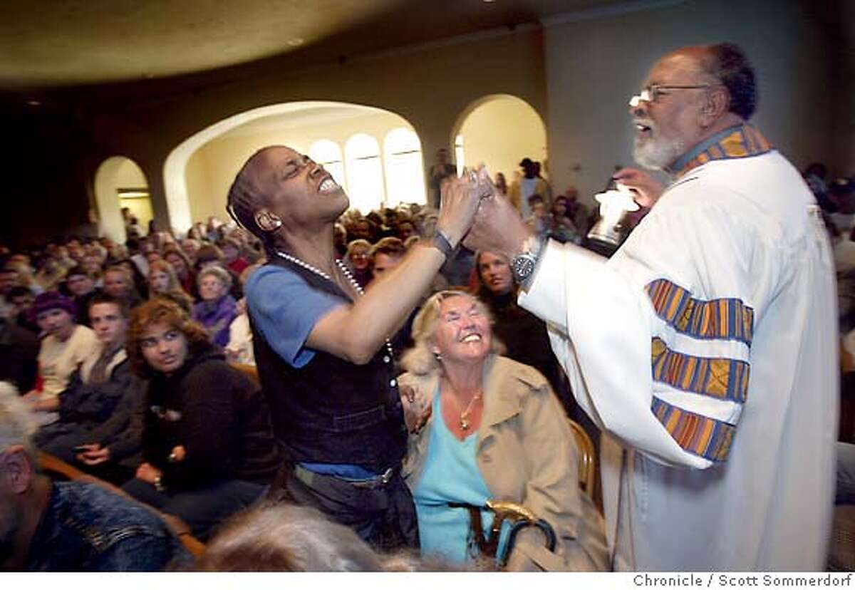 Cecil Williams blesses a young woman in the congregation while walking through the aisles with a lantern. Cecil is both a moving speaker and a bit of a showman in his sermons at Glide. SF CHRONICLE PHOTO BY SCOTT SOMMERDORF