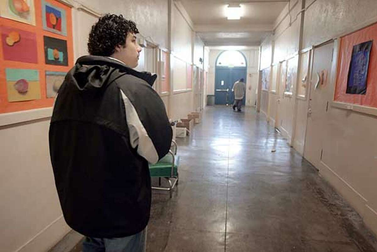 Abraham Pena, 18, walks down the halls of Street Academy in Oakland. At times he has felt he might drop out of high school like his now 22-year-old brother did years ago. 3/30/05 Mike Kepka / The Chronicle