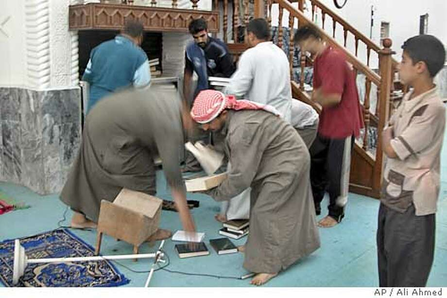 Iraqis clean up debris in a mosque in Ramadi, 113 kilometers (70 miles) west of Baghdad, Iraq,Tuesday, Oct 12, 2004. U.S. soldiers and marines raided seven mosques in and outside Ramadi suspected of harboring terrorists, storing illegal weapons caches, promoting violence and encouraging insurgent recruitment, the U.S. command said.(AP Photo/Ali Ahmed) Photo: ALI AHMED