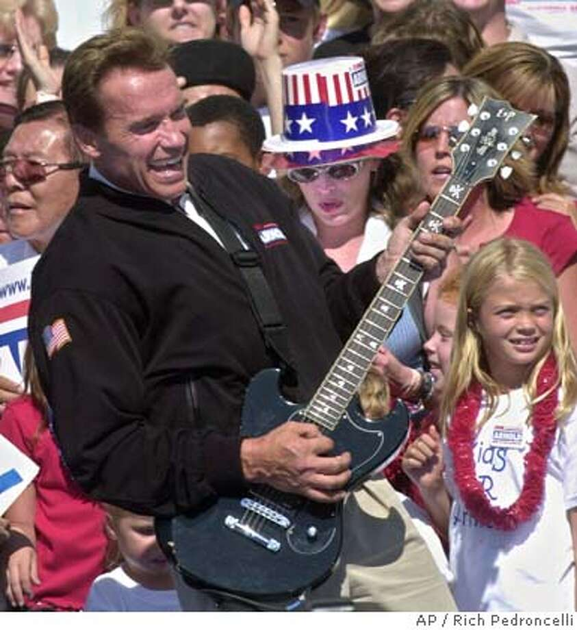 """Republican gubernatorial candidate Arnold Schwarzenegger, playfullly strums a guiter to the Twisted Sister song, """"We Ain't Going to Take it Anymore,"""" during a campaign rally held at the Capitol in Sacramento, Calif., Sunday, Oct. 5, 2003. The event was part of a four day bus tour the state before Tuesday's recall election.(AP Photo/Rich Pedroncelli) CAT Photo: RICH PEDRONCELLI"""