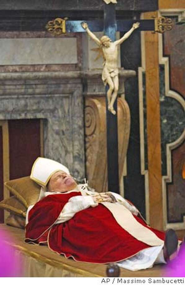 The body of Pope John Paul II lies in state in the Clementine hall at the Vatican, Sunday, April 3, 2005. The Vatican announced that John Paul died at 21:37 local time Saturday, April 2, after a long struggle against debilitating illness. He was 84. (AP Photo/Massimo Sambucetti, pool) Photo: MASSIMO SAMBUCETTI