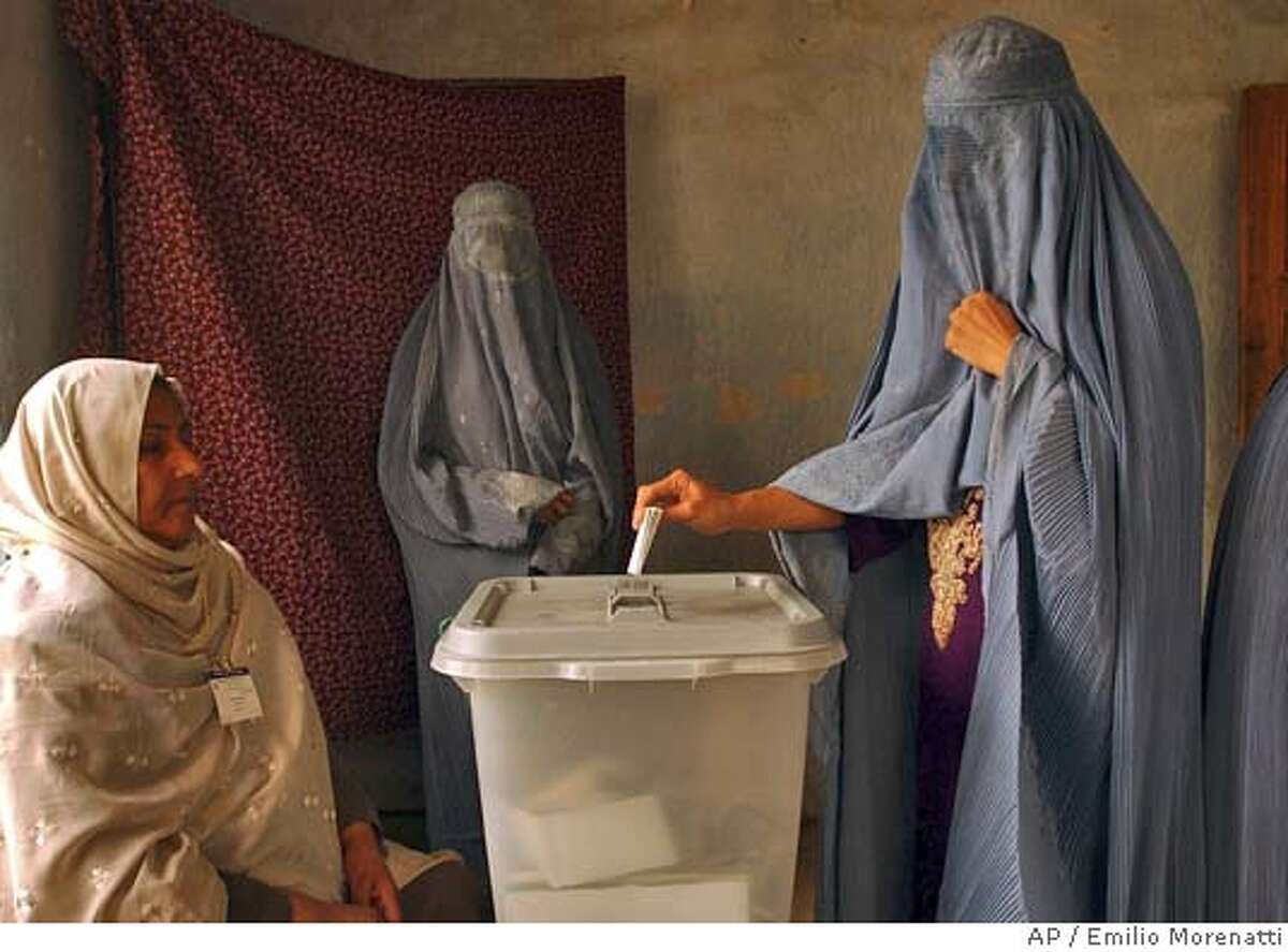 An Afghan woman wearing a burqa casts her ballot at a polling station in Kabul Saturday, Oct. 9. 2004. Across Afghanistan, voters went to the polls in the country's first-ever direct presidential elections. (AP Photo/Emilio Morenatti)