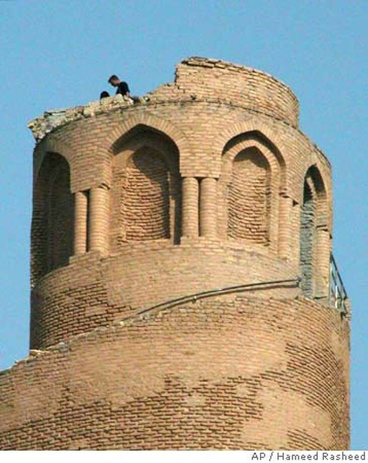 Iraqis stand atop the damaged ninth-century spiral minaret, one of Iraq's most recognized landmarks, after it was damaged by an explosion in Samarra, Iraq, Friday, April 1, 2005. Witnesses said two men climbed the 170-foot-tall (50-meter-tall) minaret, then returned to the ground before the explosion occurred. The minaret is a symbol of Samarra's past glory, the only remains of a mosque dating back from the Abbasid Islamic dynasty. (AP Photo/Hameed Rasheed) Photo: HAMEED RASHEED