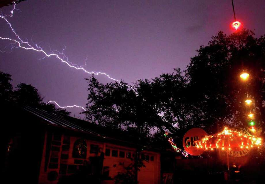 Lightning streaks across the sky in north central San Antonio as a line of thunderstorms moves through the Hill Country area early Wednesday. Rainstorms and strong winds across parts of Texas have left thousands of people without electricity. (AP Photo/San Antonio Express-News, John Davenport) (AP Photo/San Antonio Express-News) Photo: AP