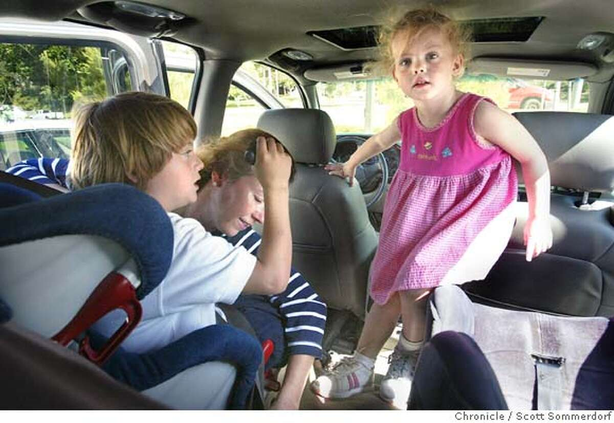 Mom's daily hectic duties. Betsy Warden locks her son Parker (left) into his car seat after a quick trip to the toy store, while her daughter Sumner (cq) finds her way to hers. Each child was able to pick out a toy because they had been good. =--=-=-=- Warden family: Mother Betsy Warden, father Bill Warden., and son Parker, and daughter Sumner (cq). Betsy and Bill lost two of their three triplets Elizabeth and William - only Parker survived. SF CHRONICLE PHOTO / SCOTT SOMMERDORF
