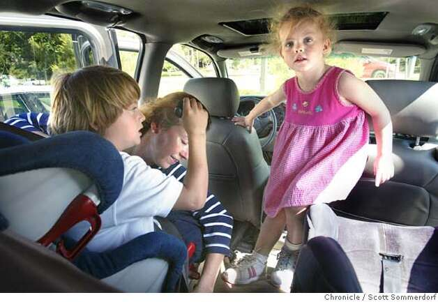Mom's daily hectic duties. Betsy Warden locks her son Parker (left) into his car seat after a quick trip to the toy store, while her daughter Sumner (cq) finds her way to hers. Each child was able to pick out a toy because they had been good.  =--=-=-=-  Warden family: Mother Betsy Warden, father Bill Warden., and son Parker, and daughter Sumner (cq). Betsy and Bill lost two of their three triplets Elizabeth and William - only Parker survived.  SF CHRONICLE PHOTO / SCOTT SOMMERDORF Photo: SCOTT SOMMERDORF