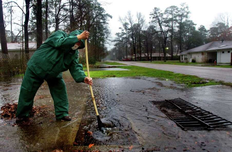 Jasper Cunningham cleans leaves out of his neighbors' drainage ditches along with his own in the Tim