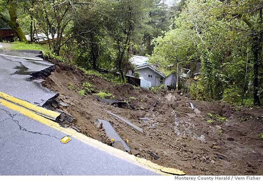 A mudlside damaged a large portion of Valencia Road in Aptos, Calif. on March 23, 2005 Damage was done to three homes forcing up to ten people to evacuate. The heavy rain has saturated the hillsides causing flooding along with mudslides. Up to ten people were evacuated from three homes in the area. (AP Photo: Vern Fisher, Monterey County Herald) Photo: Vern Fisher