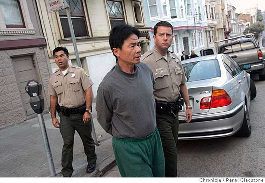 ABALONE_gladstone  officers Todd Ajari and Stacey LaFave take suspect 52 yr old Li Sheng Chen from his apt. to a car on Sacto st.  DEPT of fish and game launch one of the biggest abalone busts in recent yrs. in SF. They make one arrest at this house and look thru the suspects car.  SAN FRANCISCO on 9/30/04 by Penni Gladstone  San Francisco Chronicle Metro#Metro#Chronicle#10/1/2004#ALL#5star#b4#0422385100 Photo: Penni Gladstone