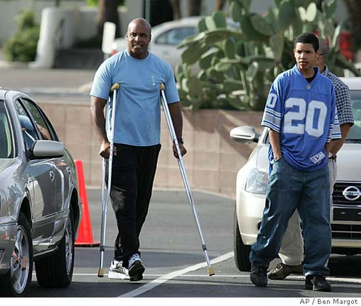 San Francisco Giants' Barry Bonds returns to spring training camp Tuesday, March 22, 2005, in Scottsdale, Ariz. Bonds has returned to Giants camp for rehabilitation since a second arthroscopic surgery on his right knee last week. At right is his son, Nikolai Bonds. (AP Photo/Ben Margot)