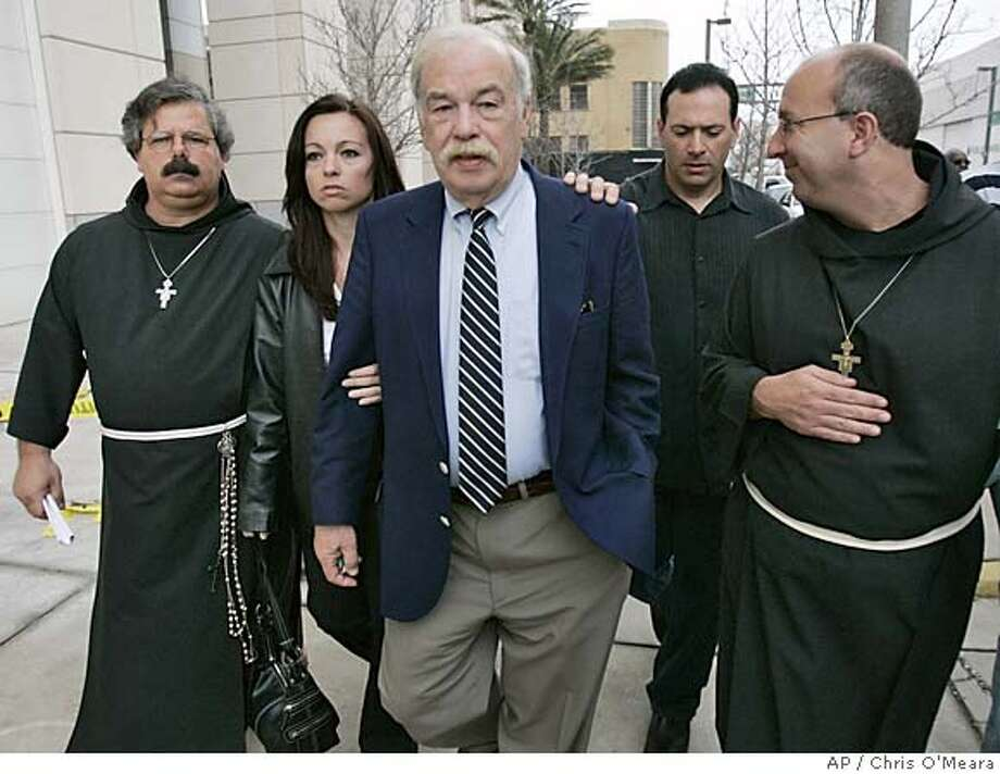 Bob Schindler, center, father of Terri Schiavo, center, walks with his daughter Suzanne Vitadamo, second from left, and his son-in-law Michael Vitadamo, and spiritual advisors Brother Hilery McGee, left, and Brother Paul O'Donnell, after a hearing at the United States Courthouse Monday afternoon March 21, 2005 in Tampa, Fla. Federal Court judge James Whittemore didn't rule on if Terri's feeding tube should be reinstated. (AP Photo/Chris O'Meara) Photo: CHRIS O'MEARA