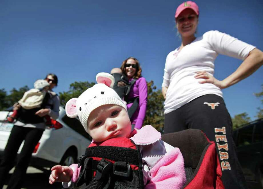 Jane Lowry, 11months, sits in her carrier as her mother, Emily Lowry, right, gets ready for a hike with Bridget Hogue, left, and Marlene Dodge, center, at Eisenhower Park. Photo: Bob Owen, San Antonio Express-News / rowen@express-news.net