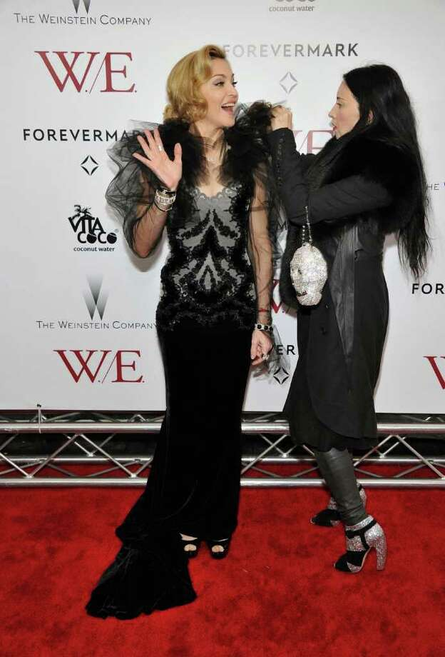"""Madonna gets some quick wardrobe help on the red carpet at The Cinema Society & Forevermark  premiere of """"W.E."""" at the Ziegfeld Theater on Jan. 23 in New York City. Photo: Theo Wargo, Getty Images / 2012 Getty Images"""