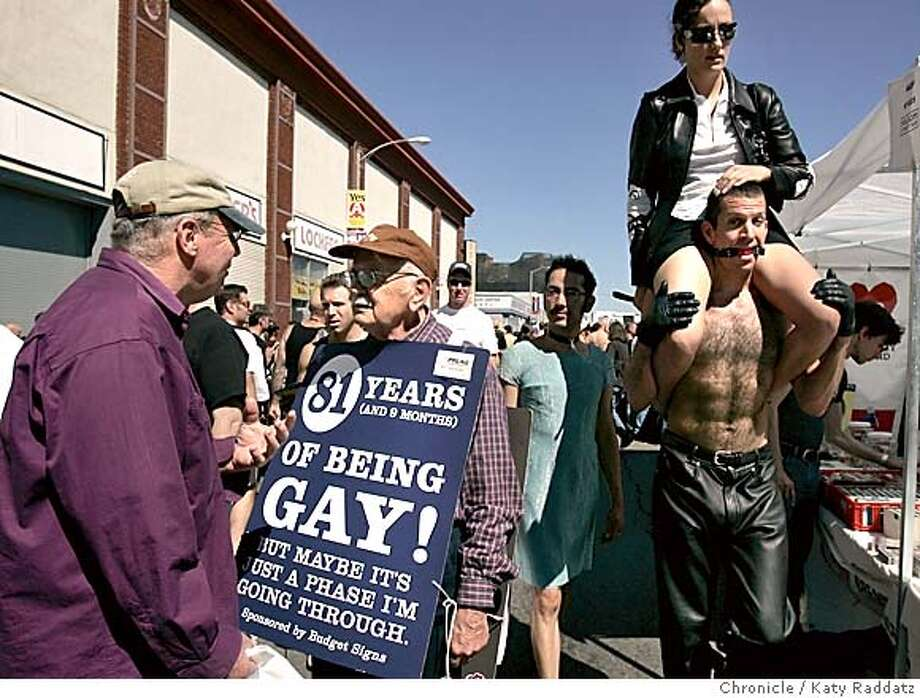 "SHOWN: Ray Kesler proudly wears his sign proclaiming 81 years of being gay. The phrase, ""but maybe it's a phase I'm going through"" comes from his volunteer work for PFLAG (Parents and Friends of Lesbians and Gays), where many anguished parents of gay children say that same thing. Ray also volunteers for Hospice By the Bay. Ray is greeting his old friend Devin Grant as the fair swirls around them. Folsom St. Fair, where the leather-bondage-punishment-everything-loving crowd comes out in force to enjoy each other. Katy Raddatz / The Chronicle Photo: Katy Raddatz"