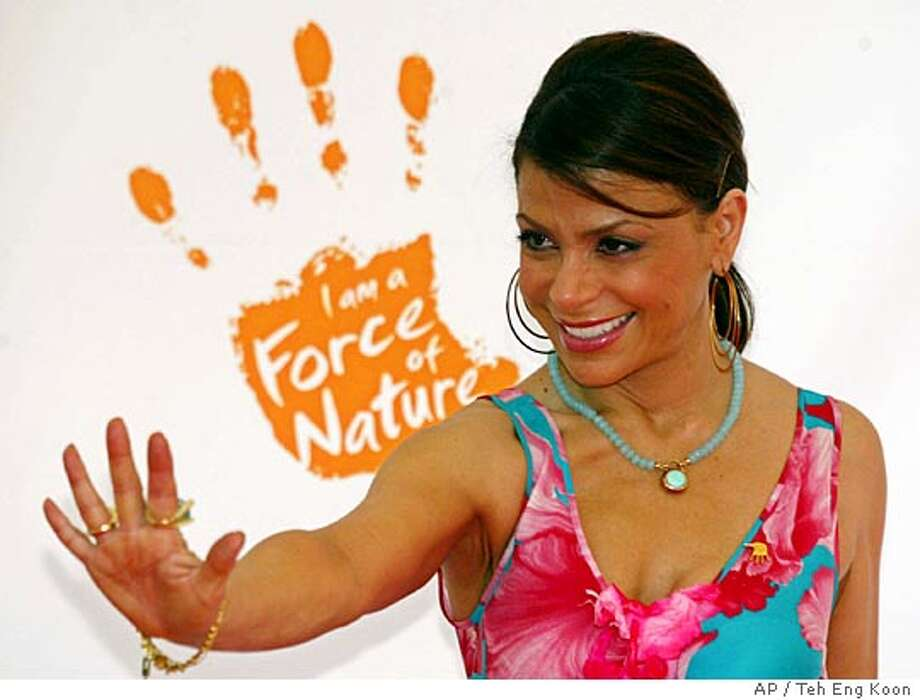 "American Idol judge Paula Abdul flashes the force of Nature Aid Foundation sign as she arrives at the charity concert for tsunami victims in Kuala Lumpur Saturday, March 19, 2005. The seven-hour ""Force of Nature"" show at Kuala Lumpur's Stadium Putra was the biggest concert in Malaysian history, marking the first initiative of a local nonprofit organization dedicated to raising funds for natural disaster survivors. (AP Photo/Teh Eng Koon) Photo: TEH ENG KOON"