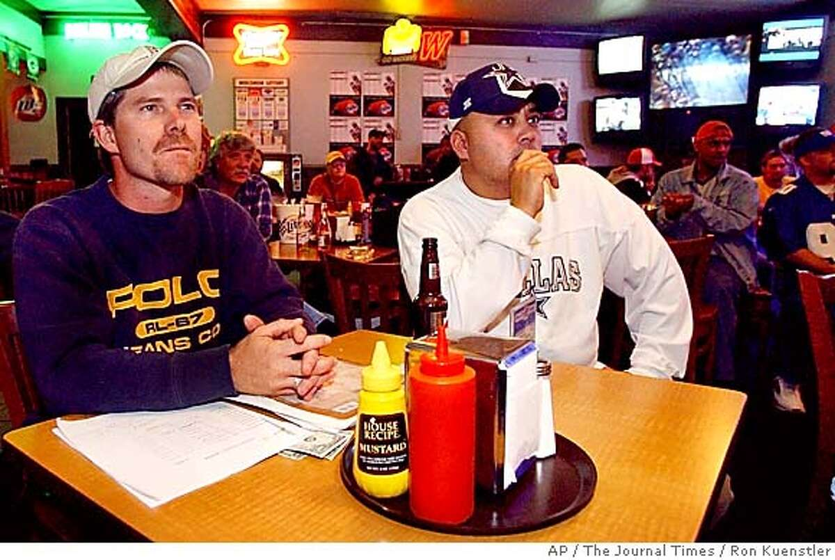 ** ADVANCE FOR WEEKEND, OCT. 11-12 ** Fantasy football players Gary Courneya, left, and Art Rodriguez, both of Burlington, Wis., watch football on some of the 24 televisions at Bucket's Pub in Racine, Wis., Sunday, Oct. 5, 2003. Courneya was primarily watching his favorite team, the Minnesota Vikings, play while keeping track of the fantasy team he plays with his co-workers.