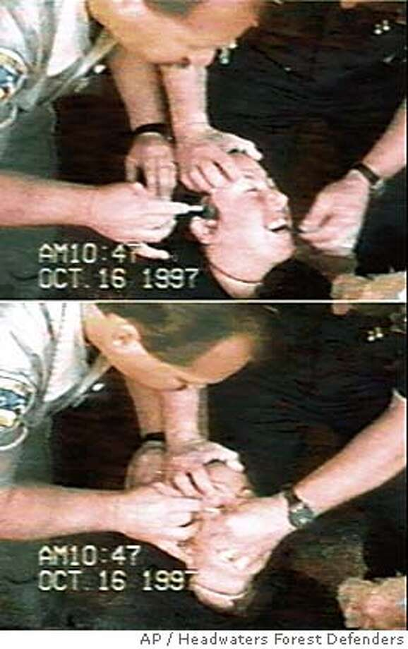 ** FILE ** These images taken from a video that was shot by the Eureka, Calif., Police Department, according to Headwaters Forest Defenders, show what Headwaters Forest Defenders allege are officers swabbing the eyes of demonstrators with liquid pepper spray at the office of U.S. Rep. Frank Riggs in Eureka, Calif., Oct. 16, 1997. Opening statements began Thursday Sept. 9, 2004, in federal court in the pepper spray retrial, in which demonstrators allege deputies swabbed pepper spray on their eyes during three protests, including the protest in Riggs' office, over Pacific Lumber Co.'s logging of ancient redwoods. (AP Photo/Headwaters Forest Defenders, File) OCT 16 1997 FILE IMAGE TAKEN FROM VIDEO PROVIDED BY HEADWATERS FOREST DEFENDERS