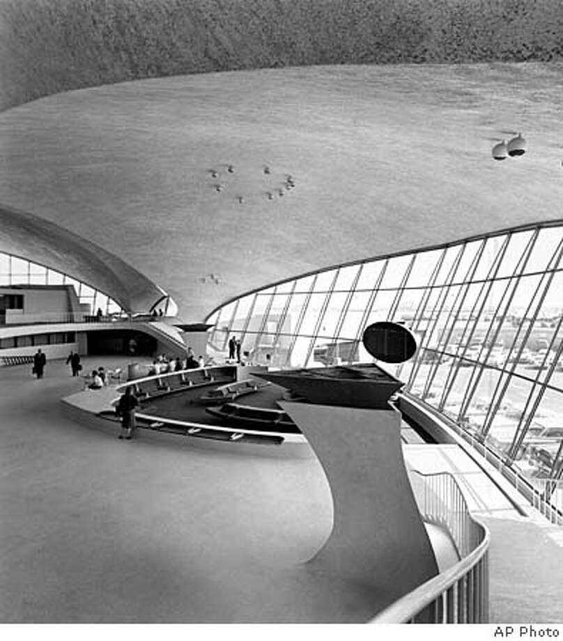 A curved ceiling and glass walls that lean out sharply onto a sweeping view of the runways and giant jet planes are the distinctive features of the lounge at Trans World Airway's new terminal buiding at New York's Idlewild Airport , May 29, 1962. (AP Photo)