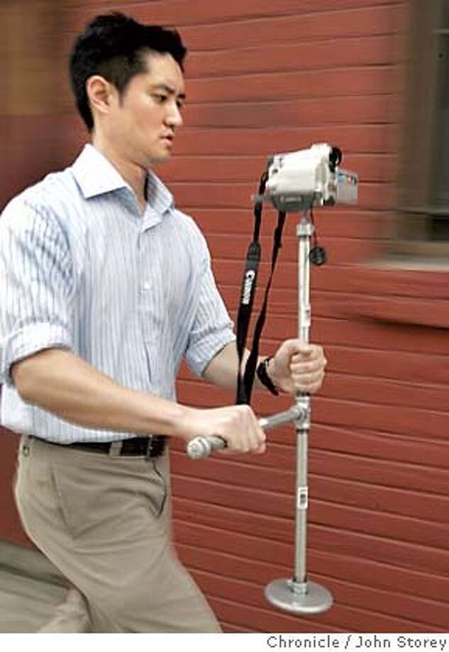 "{object name} Business writer Marcus Chan shows off the video camera stabilizer he made for $14.00. Story about the magazine ""Make"" and the tech things you can make. John Storey San Francisco Event on 3/3/05 MANDATORY CREDIT FOR PHOTOG AND SF CHRONICLE/ -MAGS OUT Photo: John Storey"