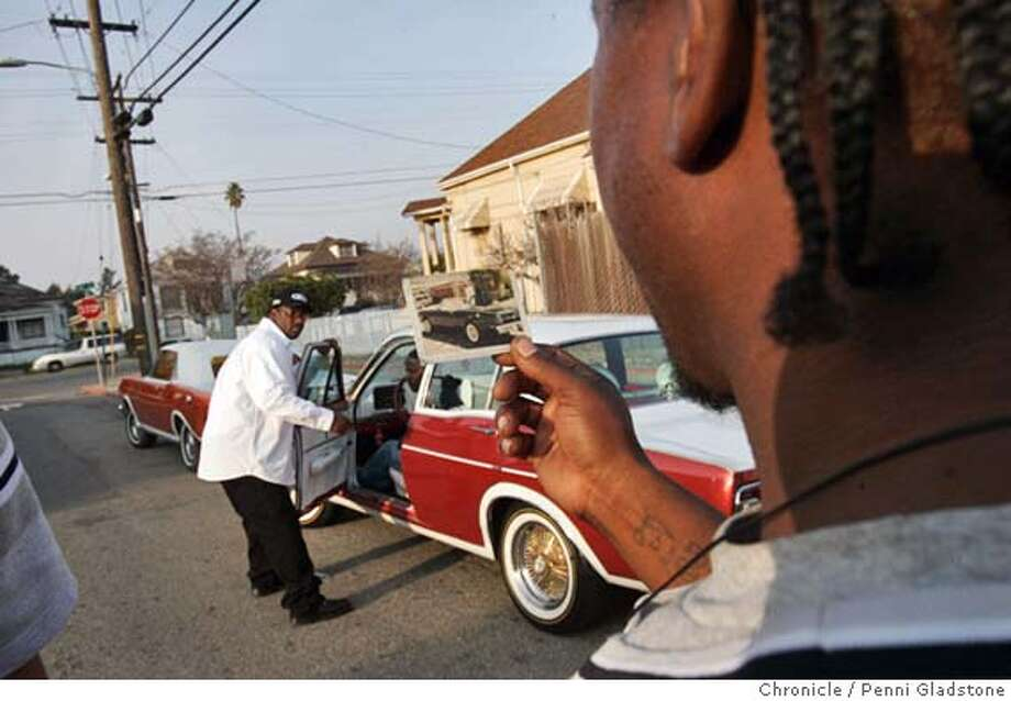 FALCONXX187PG.JPG  Corey Blacksher hold a photo of what Kenny McElroy's car used to look like before being redone.  Cruising with the Falcon Boys - the ultimate members-only club in the Oakland ghetto. men who restore and fix late 1960's Ford Falcons until they glint like gold just like their teeth.Filmmaker Brian Lilla is creating the first ever documentary about the Falcon Boy, due out early next year. The San Francisco Chronicle  Photo taken on 12/6/04, in Oakland, CA. Photo: Penni Gladstone