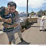 Saleh gives Raheem a hug before Raheem leaves for a driving lesson with Leslie Troutner (right). He received his driver's learners permit the day before. The Troutners have taken in Saleh and Raheem as family. Through an international rescue mission, Saleh Khalaf, 9, on the brink of death after an explosion, was flown from Iraq to Oakland Children's Hospital along with his father, Raheem. Deanne Fitzmaurice / The Chronicle  THIS IS PART OF A PROJECT ABOUT THIS IRAQI BOY. DO NOT USE ELSEWHERE.