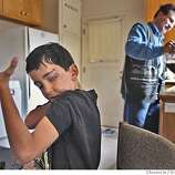 Saleh flexes his muscle as Raheem pours coffee in the kitchen of their new apartment in Oakland. Through an international rescue mission, Saleh Khalaf, 9, on the brink of death after an explosion, was flown from Iraq to Oakland Children's Hospital along with his father, Raheem. This was shot in Oakland.  Deanne Fitzmaurice / The Chronicle