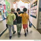 Saleh walks the halls of Park Day School in Oakland with his new buddies. At left, Owen Clark, and at right, Austin Bisharat. Through an international rescue mission, Saleh Khalaf, 9, on the brink of death after an explosion, was flown from Iraq to Oakland Children's Hospital along with his father, Raheem. This was shot in Oakland.  Deanne Fitzmaurice / The Chronicle