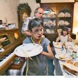 Saleh clears his plate off the table after dinner with Leslie and Daniel Troutner. The Troutner's have taken Saleh and Raheem in as family. Through an international rescue mission, Saleh Khalaf, 9, on the brink of death after an explosion, was flown from Iraq to Oakland Children's Hospital along with his father, Raheem. Deanne Fitzmaurice / The Chronicle