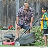 Daniel Troutner supervises while Saleh mows the Troutner's front lawn. The Troutner's have taken in Saleh and Raheem as family. Through an international rescue mission, Saleh Khalaf, 9, on the brink of death after an explosion, was flown from Iraq to Oakland Children's Hospital along with his father, Raheem. Deanne Fitzmaurice / The Chronicle
