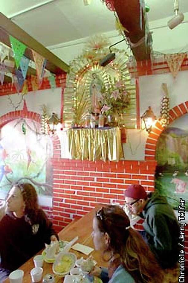 A festive altar, vibrant murals and bright pennants make Taqueria Cancun an attractive place to have a burrito. Chronicle photo by Jerry Telfer / CHRONICLE
