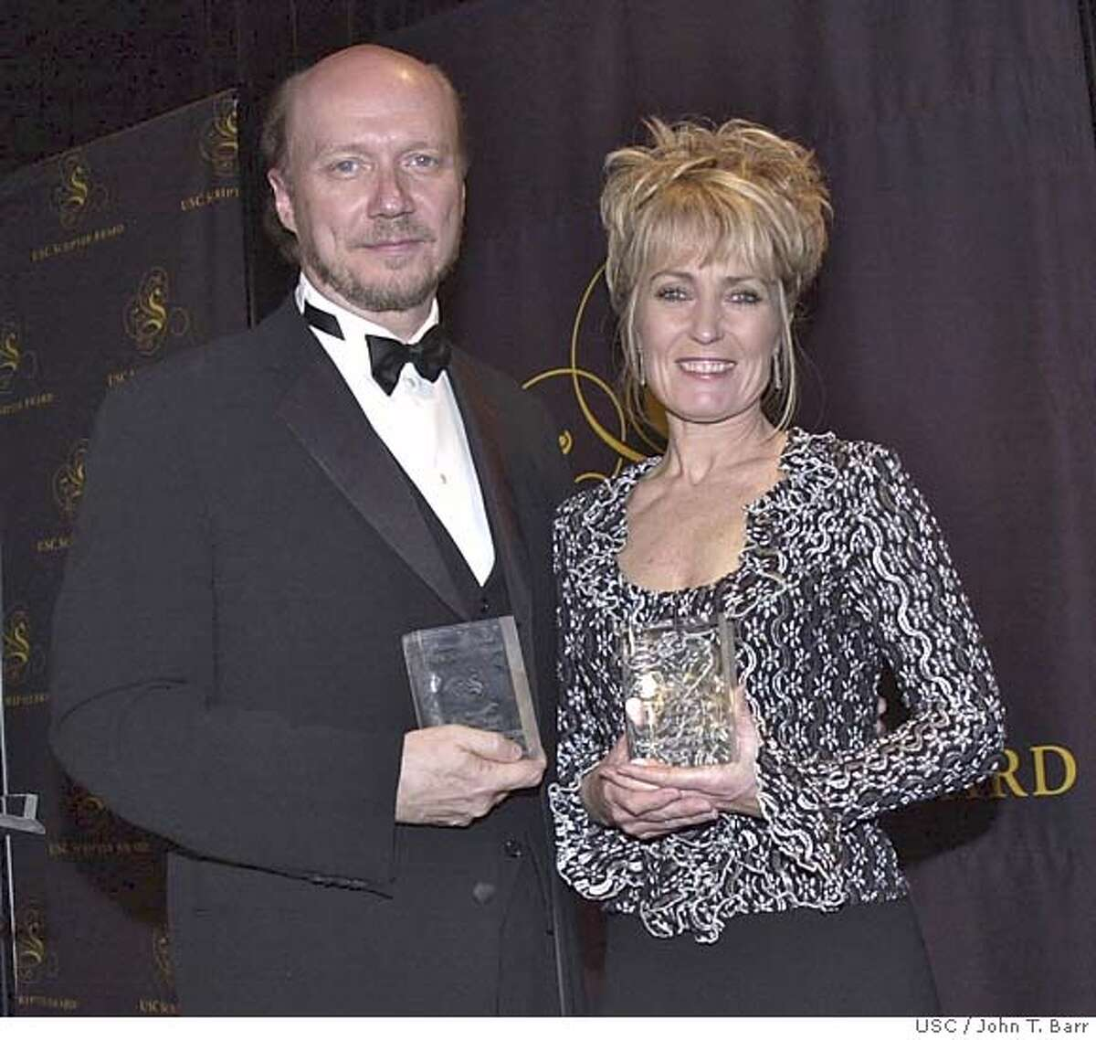 """The writers of """"Million Dollar Baby"""" receive the 17th annual , a prize that honors both author , F.X. Toole, and screenwriter Paul Haggis(L) for best adaptation of a book or short story to film late Sunday, February 20, 2005. At right is Erin Boyd, daughter of the late author Jerry Boyd(a.k.a. F.X.O'Toole) accepting the award for her father. The annual blacktie gala was held in the Edward L. Doheny Jr. Memorial Library on the USC campus"""