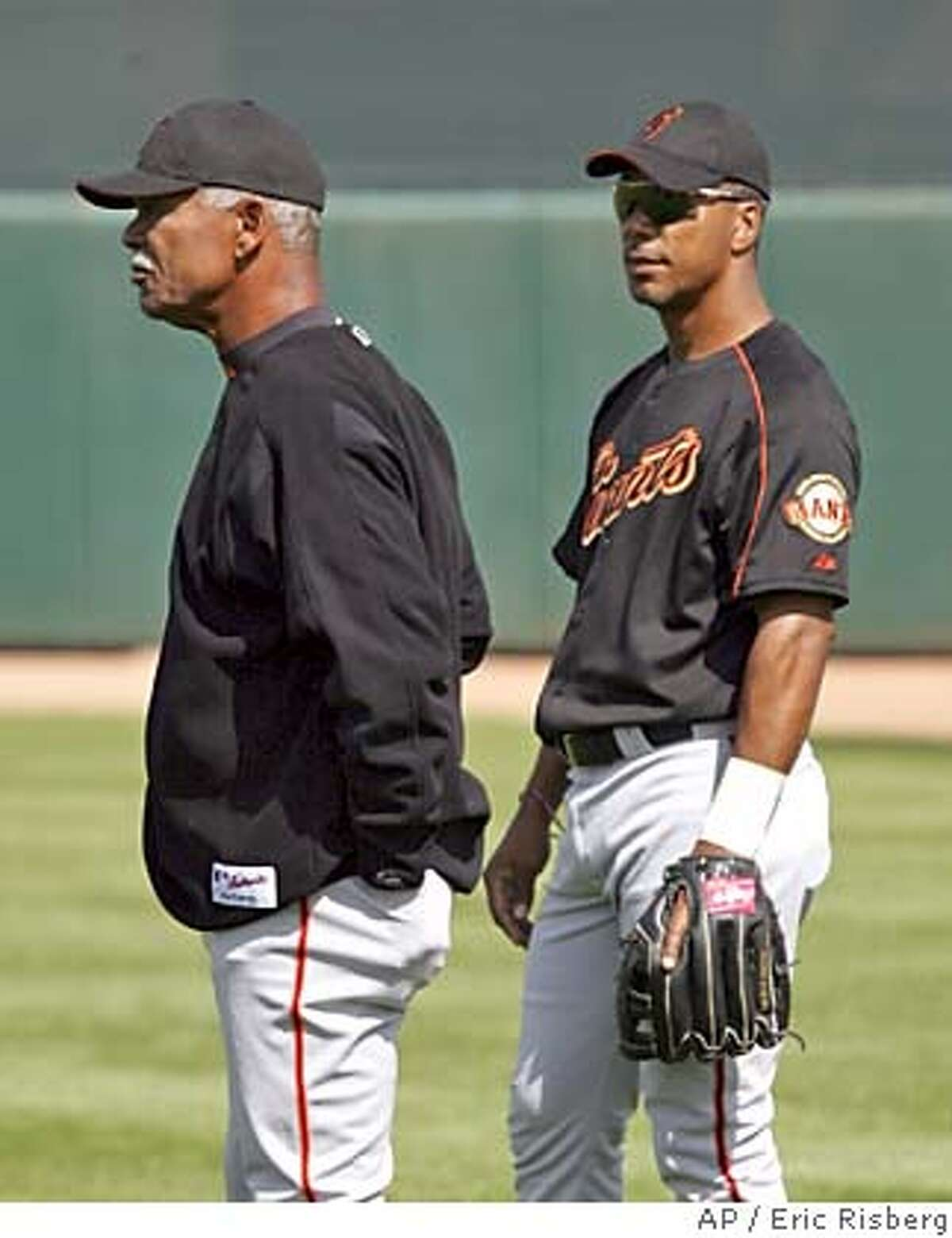 San Francisco Giants manager Felipe Alou, left, stands with his son, Giants right fielder Moises Alou, right, in right field at Scottsdale Stadium during spring training in Scottsdale, Ariz., Monday Feb. 28, 2005. (AP Photo/Eric Risberg)