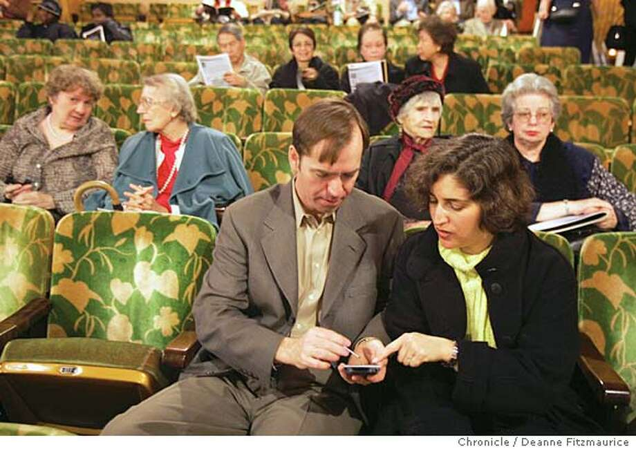 Before the concert begins, Michael and Deborah Sosebee from Oakland try out the device. The Concert Companion is a handheld device that displays text and video in real-time during a performance. They were available for use at the Paramount Theater during a performance by the East Bay Symphony. Deanne Fitzmaurice / The Chronicle Photo: Deanne Fitzmaurice