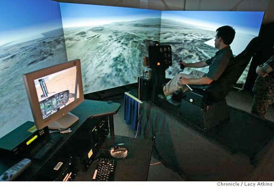 "Erik Johnson shows how the ""Distributed Rendering in a Cave Virtual Reality"",project works which works with a Delta 3D software created by the Move Institute, in Monterey, Aug.25,2004. The MOVES Institute (Modeling,Virtual Environments and Simulation) holds it's open house demonstrating the latest hightech equipment and techniques designed for military training, Aug.25, 2004, in Monterey.  LACY ATKINS/ The Chronicle Photo: LACY ATKINS"