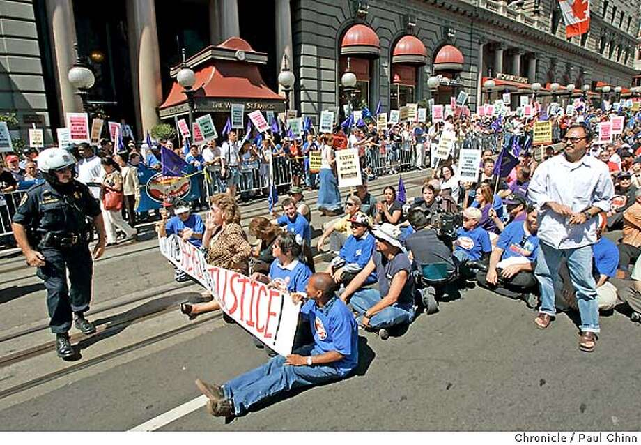 At left, a police officer keeps watch over about 150 protesters that sat down in the middle of Powell St. blocking off traffic in front of the St. Francis Hotel (background). About 150 hotel workers and union activists from SEIU Local 2 were arrested after sitting down on the cable car tracks in front of the St. Francis Hotel on 9/6/04 in San Francisco, CA. PAUL CHINN/The Chronicle Photo: PAUL CHINN