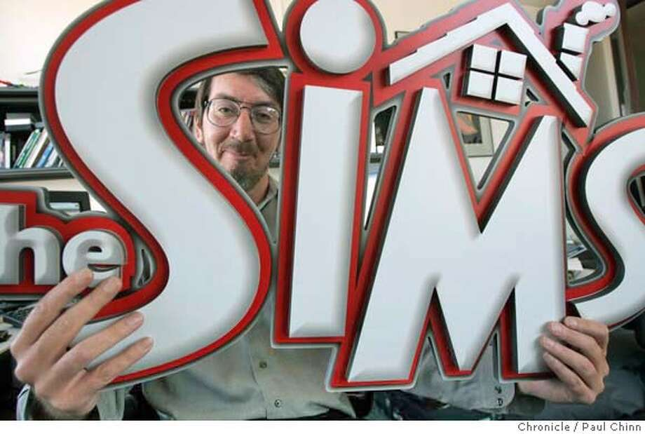 """Will Wright peeks through the logo from the original """"The Sims"""" game. Wright's latest game is a sequel to the popular simuation game. Computer game designer Will Wright at Maxxis offices in Walnut Creek on 8/24/04. PAUL CHINN/The Chronicle Photo: PAUL CHINN"""
