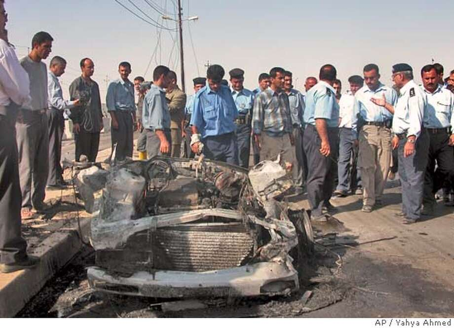 Policemen look at a vehicle damaged by a car bomb which exploded, killing at least 20 and wounded 36 others, in Kirkuk, Iraq, Saturday Sept. 4, 2004. A suicide attacker detonated the car bomb outside a police academy as hundreds of trainees and civilians were leaving for the day. (AP Photo/Yahya Ahmed) Photo: YAHYA AHMED