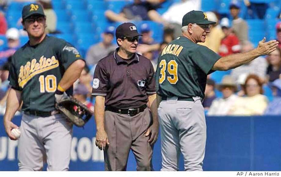 Oakland Athletics manager Ken Macha, right, exchanges words with first base umpire Ed Rapuano, center, after Toronto Blue Jays Carlos Delgado was called safe at first base during sixth inning AL action in Toronto Sunday Sept. 5, 2004. Athletics first baseman Scott Hatteberg is seen at left. The Blue Jays beat the Athletics 13-5. (AP PHOTO/Aaron Harris) Photo: AARON HARRIS