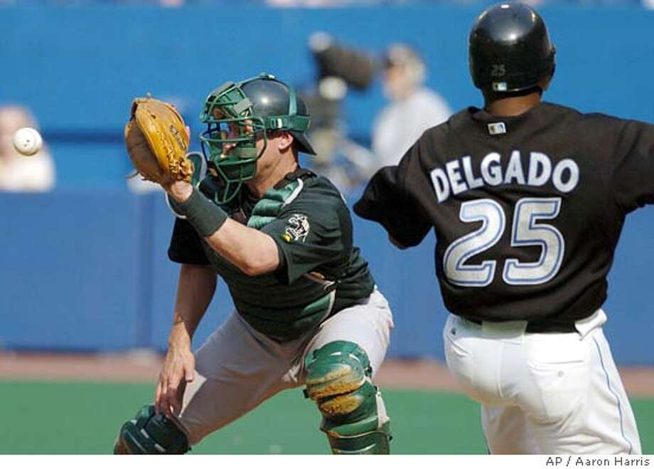 Oakland Athletics catcher Damian Miller, left, waits on the throw as Toronto Blue Jays Carlos Delgado slides into homeplate during first inning AL action in Toronto Saturday Sept. 4, 2004. Delgado was out on the play. (AP PHOTO/Aaron Harris) Photo: AARON HARRIS