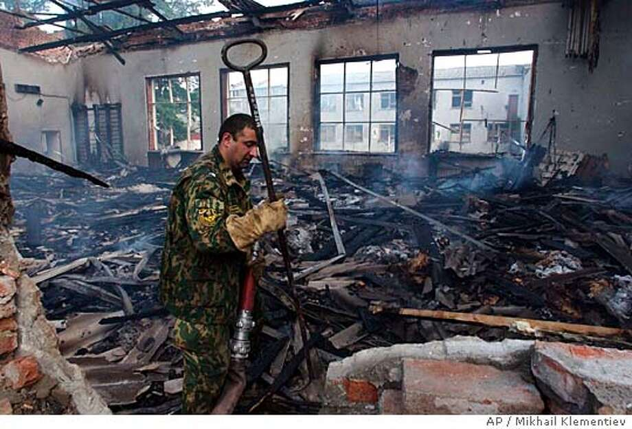 An emergency worker looks through debris and damps down fires at the destroyed sport hall of a school in Beslan, North Ossetia, Friday, Sept. 3, 2004. Officials said at least 250 people had been killed and more than 500 wounded in the crisis in Beslan, which ended in a wave of violence Friday, and there were fears the toll would rise. (AP Photo/Mikhail Klementiev/GAZETA) ** RUSSIA OUT ** Photo: MIKHAIL KLEMENTIEV