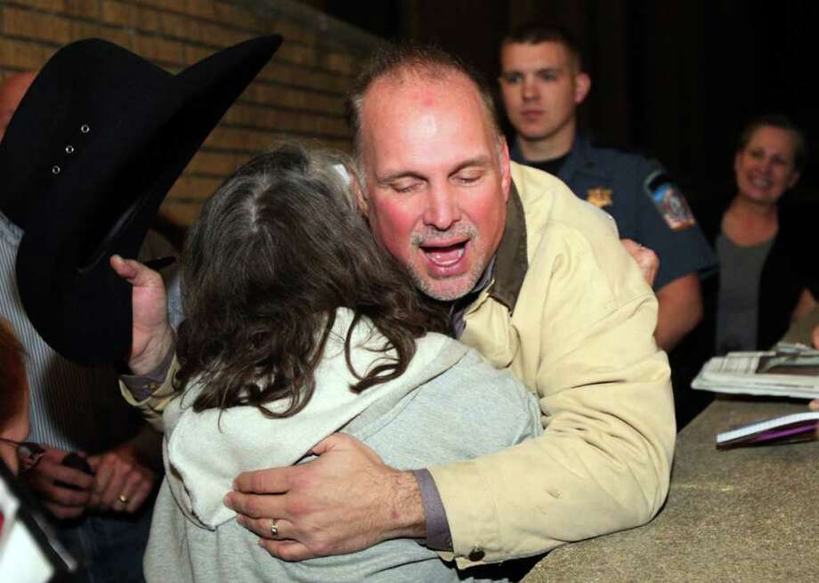Garth Brooks is hugged by a fan outside the Rogers County Courthouse, in Claremore, Okla, on Tuesday, Jan. 24, 2011.   Jurors on Tuesday evening ruled that the hospital must return Brooks' $500,000 donation plus pay him $500,000 in punitive damages.  The decision came in Brooks' breach-of-contract lawsuit against Integris Canadian Valley Regional Hospital in Yukon. Brooks said he thought he'd reached a deal in 2005 with the hospital's president, James Moore, but sued after learning the hospital wanted to use the money for other construction projects. (AP Photo/The Tulsa World, Cory Young) Photo: Cory Young