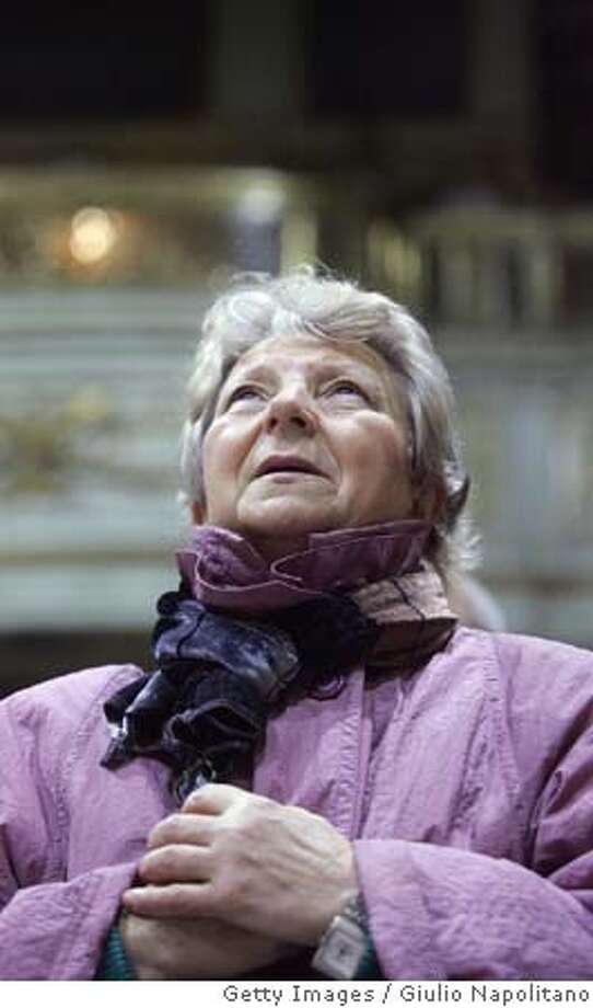 A Polish woman prays during a mass at the Polish Saint Stanislaw church, central Rome, 25 February 2005. Pope John Paul II was readmitted Thursday and underwent a tracheotomy to relieve severe breathing problems at Gemelli hospital in Rome. The Vatican provided an upbeat assessment of Pope's condition Friday saying the 84-year-old pontiff spent a restful night in hospital, although his throat surgery meant he can now only communicate his intentions by writing notes. AFP PHOTO/ GIULIO NAPOLITANO (Photo credit should read GIULIO NAPOLITANO/AFP/Getty Images) Photo: GIULIO NAPOLITANO