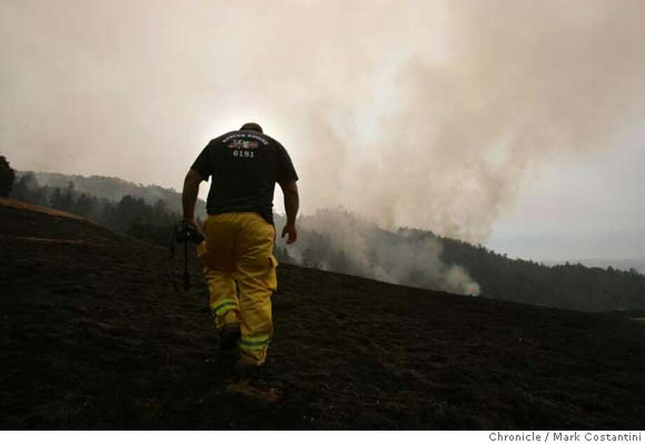 CHRISTIAN SPANGENBERG, A PHOTOGRAPHER WITH THE GEYSERVILLE FIRE DEPT. CLIMBS A BURNED HILLSIDE AS THE FIRE BURNES ON THE NEXT HILL.  THE LOCATION IS OFF PINE FLAT ROAD NEAR JIMTOWN IN SONOMA COUNTY  HUGE FIRE IN SONOMA AND LAKE COUNTY.  Event on 9/5/04 in SONOMA COUNTY. S.F. Chronicle Photo: Mark Costantini Photo: Mark Costantini