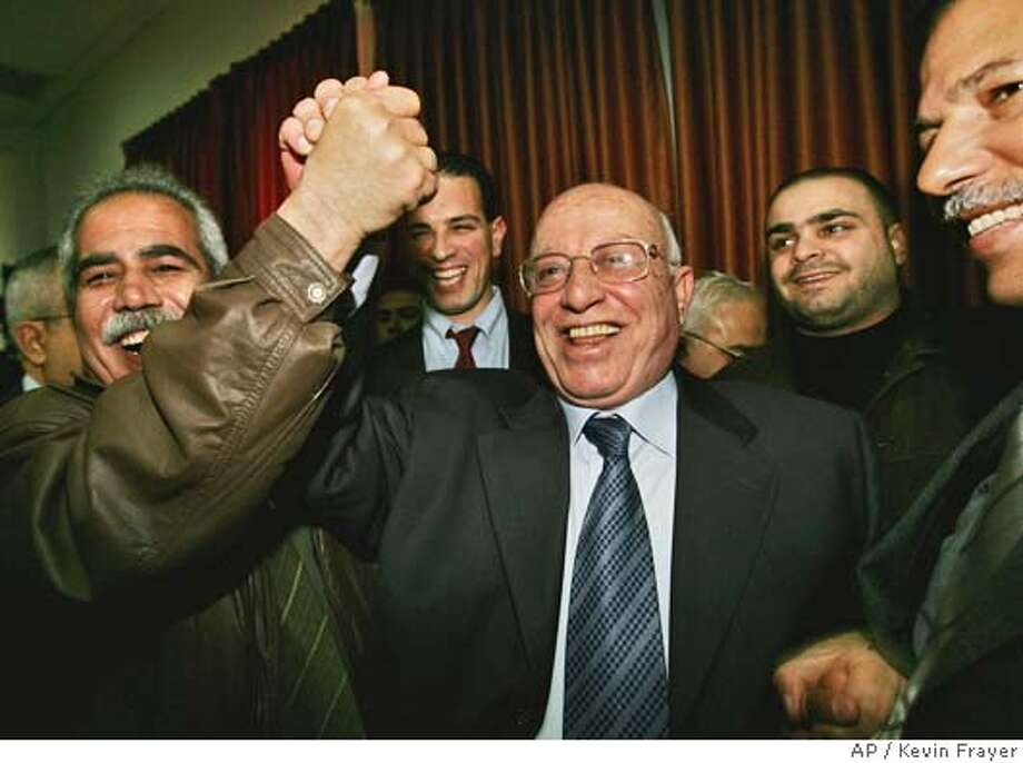 Palestinian Prime Minister Ahmed Qureia, center, and Parliament member Jamil Shati raise their hands in celebration after the Palestinian Legislative Council voted to approve the new cabinet in the West Bank town of Ramallah, Thursday, Feb. 24,2005. The Palestinian parliament on Thursday approved a 24-member Cabinet dominated by professional appointees, including nearly half with doctoral degrees, in a major move toward long-promised government reform.(AP Photo/Kevin Frayer) Photo: KEVIN FRAYER