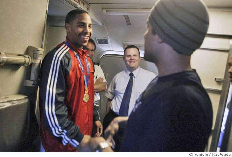 ANDREWARD_01_0039_KW.jpg (Lleft) USA Boxing Gold Medalist returns home to Oakland a hero and greets passenger Justin Brown, 28, of Hayward a friend of Wards Cousin , after the passengers applauded and cheeredd for him on his flight 435 from Denver. Photo By Kat Wade